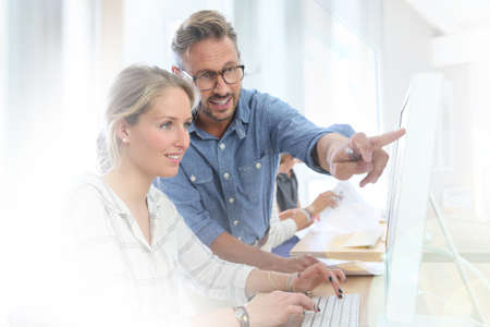 profesor alumno: Muchacha del estudiante con el profesor trabaja en el ordenador de escritorio Foto de archivo