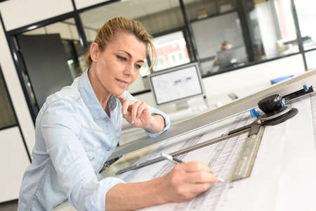 architect: Architect woman working on drawing table