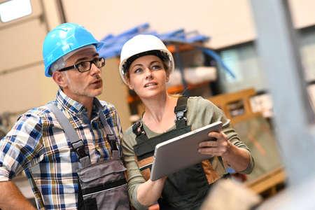 Ingenieurs in magazijn controleert voorraad met tablet Stockfoto