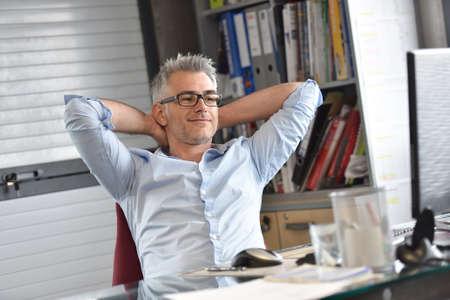 El hombre de negocios se relaja en frente de escritorio Foto de archivo