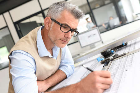 business casual: Architect sitting at drawing table in office