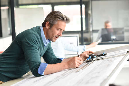 architect drawing: Architect in office working on drawing table