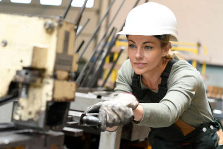 woman working: Woman with helmet working in metallurgy factory