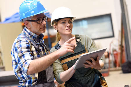 manufacture: Engineers in warehouse checking stock with tablet Stock Photo