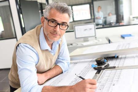 Architekt sitzt am Zeichentisch im Büro