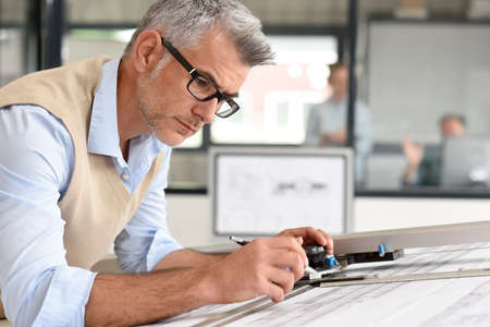 architect drawing: Architect sitting at drawing table in office