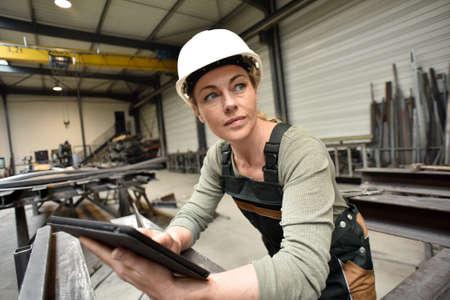 industries: Metalworker woman in factory using tablet