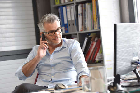 45 years old: Businessman in office talking on phone