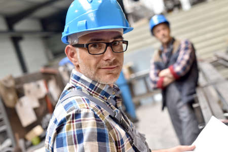 steelworks: Closeup of steelworks manager looking at plan