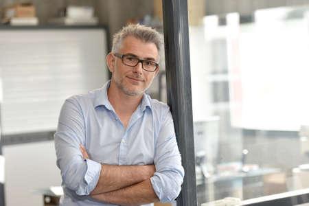 Portret van zakenman zit in kantoor Stockfoto