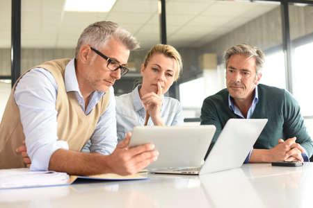 Les gens d'affaires lors d'une réunion en utilisant la tablette Banque d'images