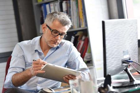 Businessman sitting in office working on tablet Zdjęcie Seryjne
