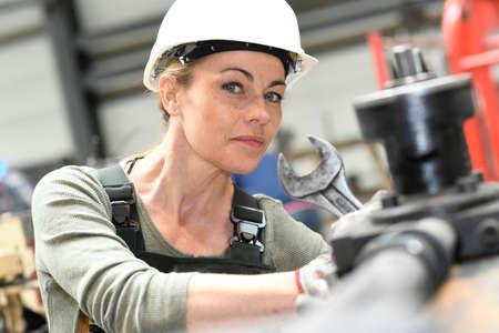 mujer trabajadora: Mujer con el casco de trabajo en la fábrica metalúrgica Foto de archivo
