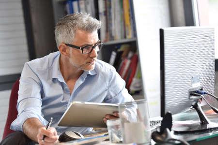 Biznesmen siedzi w biurze pracy na tablecie