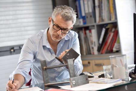 45 years old: Industrial manager in office working on metal design Stock Photo