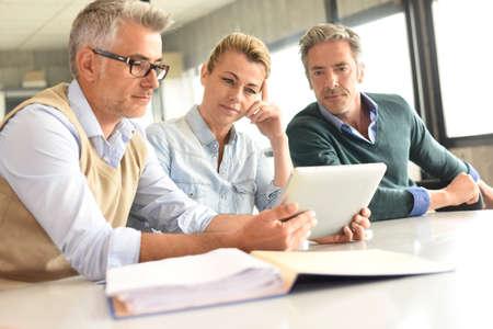 Geschäftsleute in einer Sitzung mit dem Tablet