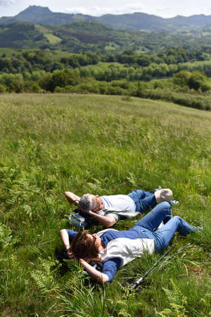 woman laying: Senior couple relaxing in field on hiking day Stock Photo