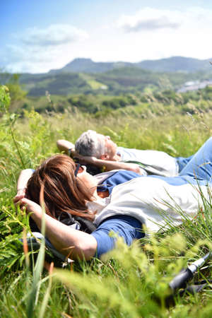 rambling: Senior couple relaxing in field on hiking day Stock Photo
