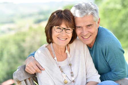 Matrimonios de edad con gafas sentado fuera