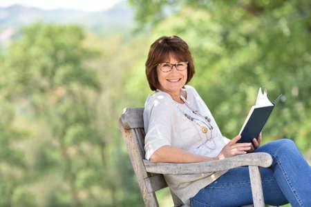 Senior vrouw leesboek buiten Stockfoto