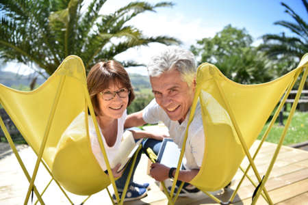 lawn chair: Senior couple relaxing in lawn chairs outside Stock Photo