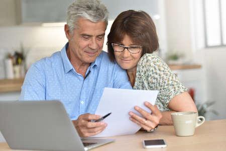 年配のカップルが自宅でラップトップ コンピューターを使用して