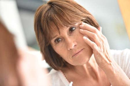 beautycare: Senior woman applying eye concealer