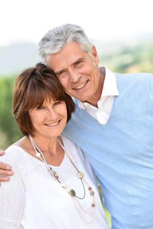 pareja abrazada: Pares mayores que abrazan el uno al otro fuera