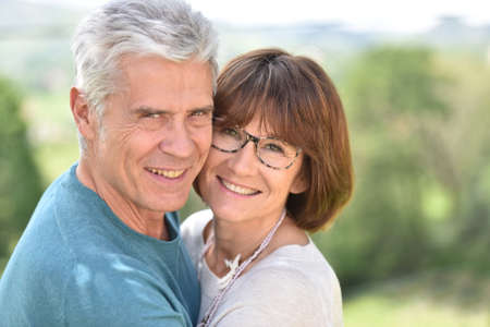 happy seniors: Senior couple embracing each other outside