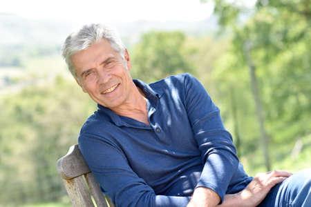 Senior homme de détente dans chaise à l'extérieur