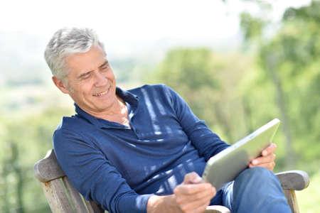 websurfing: Senior man websurfing on tablet outside Stock Photo