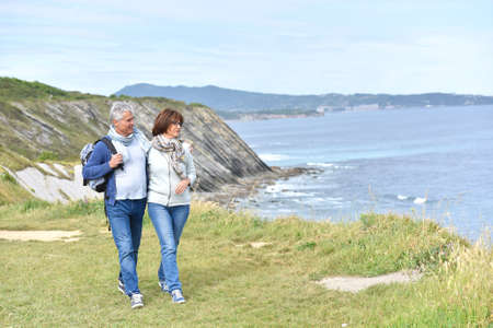 sea cliff: Senior couple walking by sea cliff