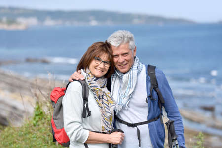 seaside: Smiling senior hiking couple standing by cliff Stock Photo