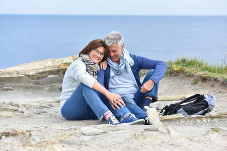 couples hug: Senior couple on rambling day sitting by cliff