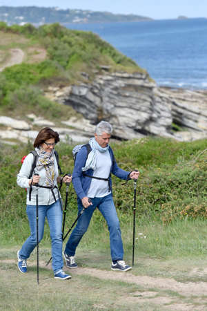 rambling: Senior couple walking on hiking track by the coast