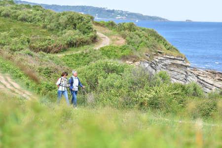sea beach: Senior couple walking on hiking track by the coast