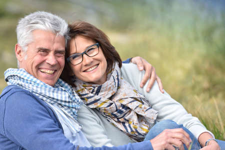 couples hug: Cheerful senior couple sitting in grass