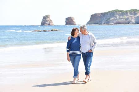 happy seniors: Senior couple walking on the beach