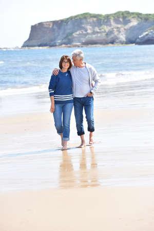 pareja abrazada: Pares mayores que recorren en la playa