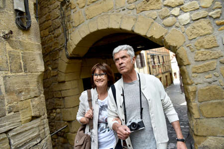 visiting: Senior couple of tourists visiting spanish little town