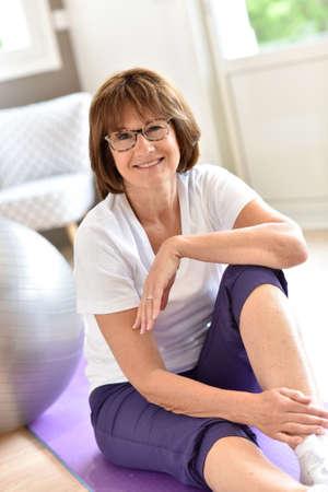 Ältere Frau mit Fitness-Ball sitzt