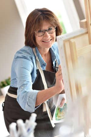 art activity: Senior woman painting on canvas Stock Photo