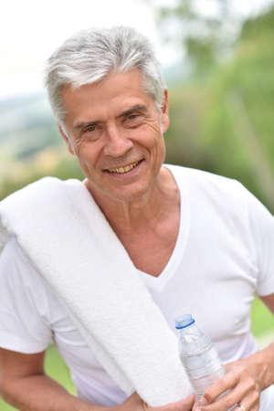 man drinking water: Senior man drinking water after exercising Stock Photo