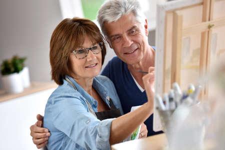 beside: Senior woman painting on canvas, husband beside