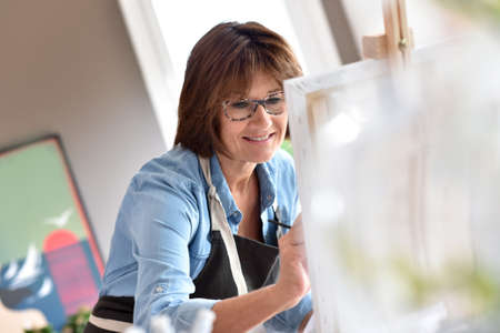 canvas painting: Senior woman painting on canvas Stock Photo
