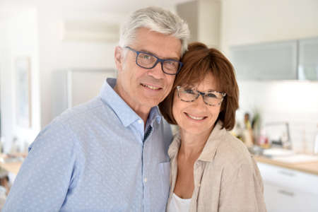 couples hug: Portrait of happy senior couple standing in kitchen