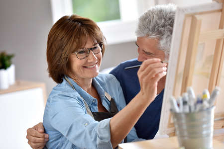 canvas painting: Senior woman painting on canvas, husband beside