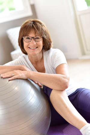 fitness ball: Senior woman sitting by fitness ball