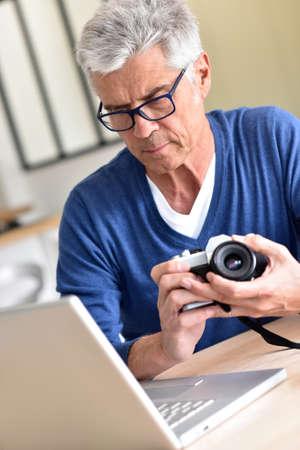 uploading: Senior man uploading pictures on laptop