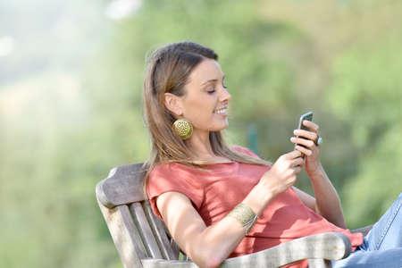 mujer sentada: Mujer hermosa en la silla al aire libre con smartphone
